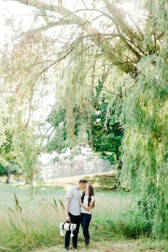 engagement session couple kissing under the weeping willow
