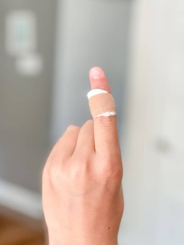 A vertical shot of a close up of a hand with one finger up, with a DIY wart bandaid on it.