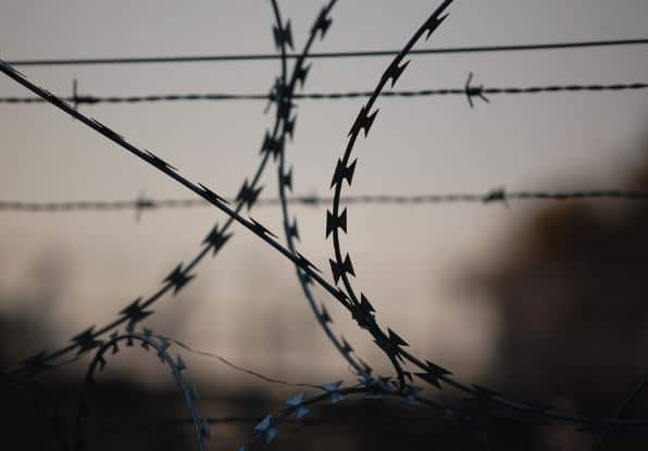 Image of barbed wire on a perimeter security fence.