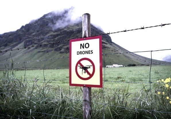 Image of no drones sign on a security fence