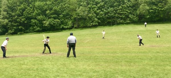 Men on a field in cooperstown, ny playing baseball in historicl costumes and with historic gear and rules.