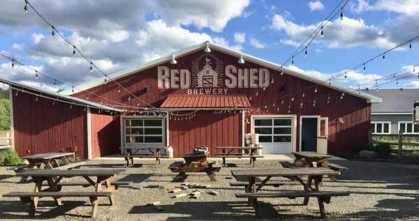 The barn-like Red Shew Brewery with its beer garden in front it; it has picnic tables and lights.
