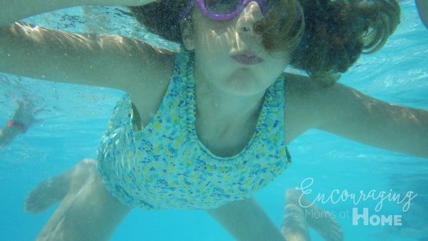 At the pool, girl swimming underwater. Twenty tips for Moms at the pool