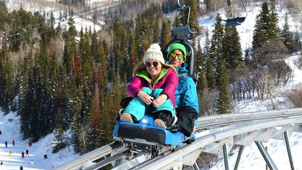 A couple rides the outlaw mountain coaster at steamboat resort in winter.