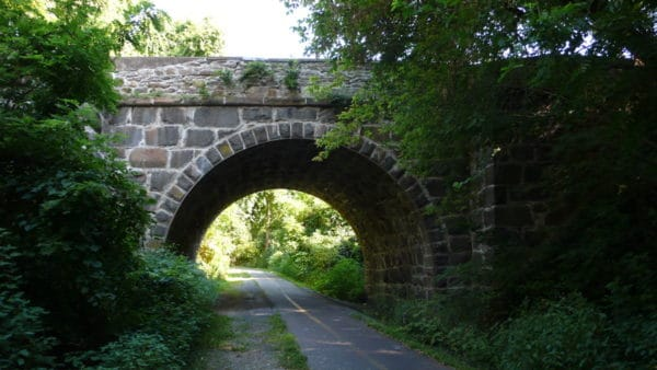 A stone bridge overpass on a more rural stretch of the washingtong and old dominion trail.