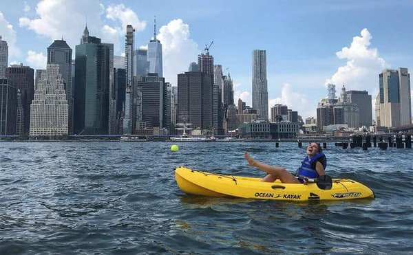 A girl has fun kayaking in the east river with manhattan behind her.