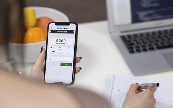 Freelancer using invoicing app on iPhone
