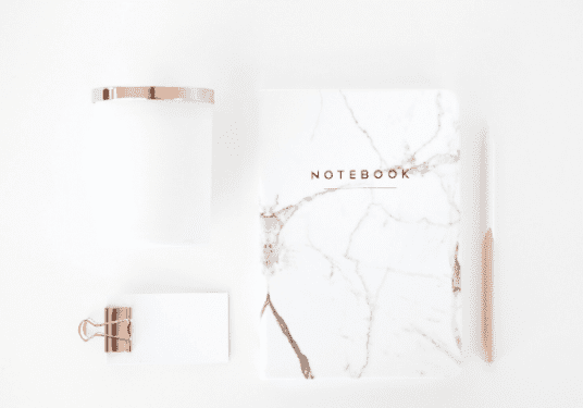 Marble patterned notebook styled alongside notepad