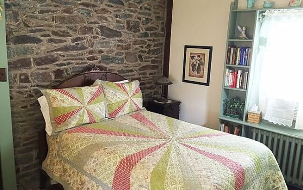 One of the cozy rooms at the lgbt-friendly wishing well b&b in new hope, pa has a retro bed spread, stone wall and pale turquoise trim.