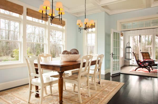 timeless wooden kitchen and dining room combo with pastel turquoise walls and warm lights