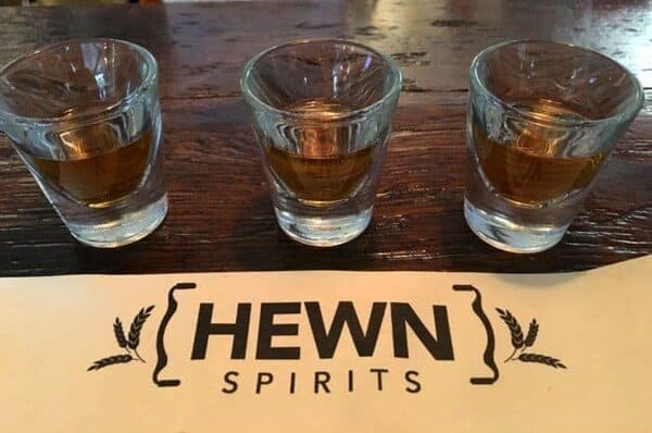 A flight of bourbon, rye and rum in shotglasses at hewn spirits at peddler's village in new hope.