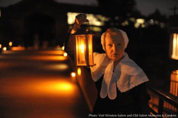 Lanterns light the way for ghosts and people in old salem, nc on annual halloween night watchmen tours.