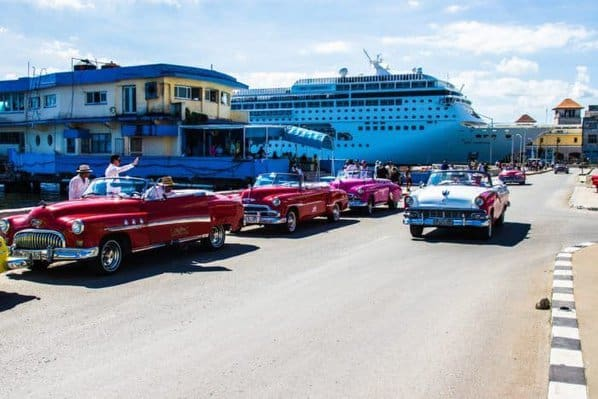 Classic cars park in front of havana's cruise ship port