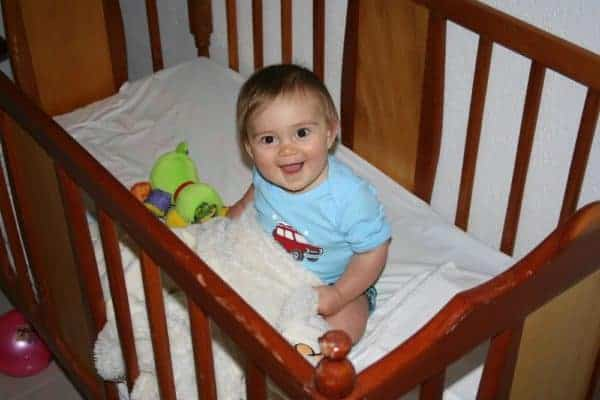 Happy baby in his crib waking up in the morning