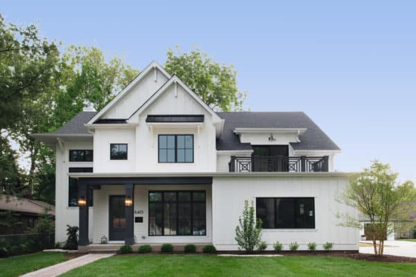 a small cozy white siding house with modern-look black windows as the accent