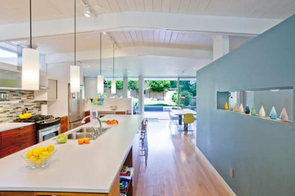 midcentury kitchen with blue accent wall and yellow lighting for a cozy feel
