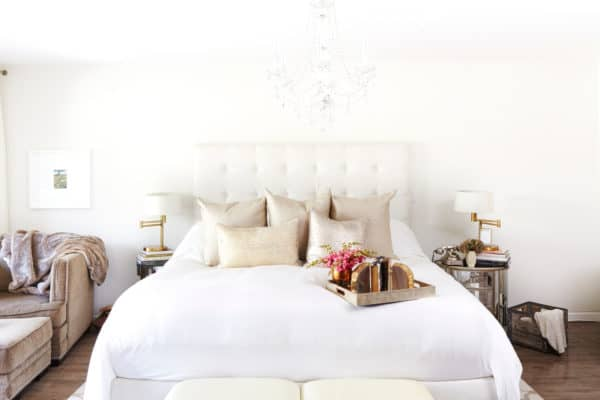 white bed and gold pillows on a dark wood floor for expensive-looking bedroom