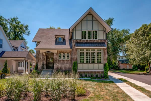 classic two-story red brick house matches its attractive red shingle roof creates countryside charm