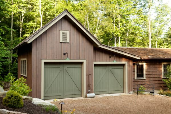 exquisite barn-inspired garage doors in sherwin williams garden gate (sw6167) with spanish moss siding for a rustic style