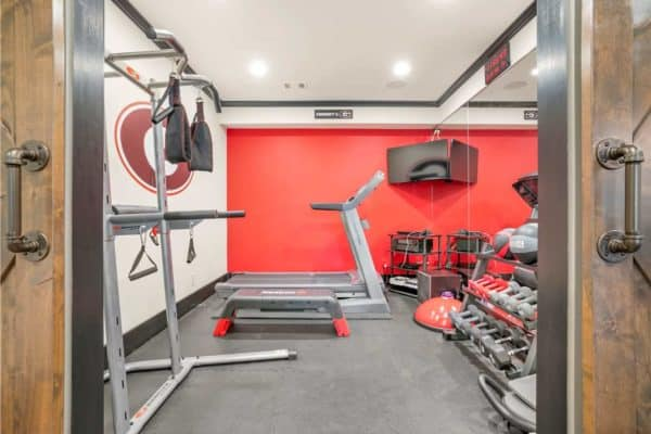Basement gym with mirrored wall, and rubber flooring.