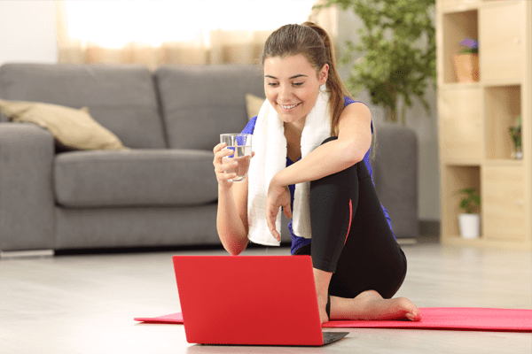 Lady with red laptop chatting to her PT via Skype after a workout sessions