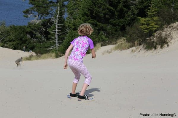 A girls plays in the oregon dunes, outside of florence.