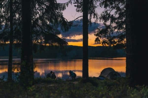 A family camping by a lake at dusk