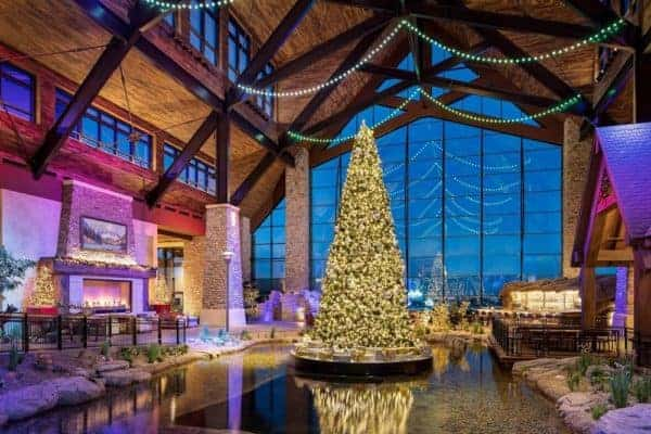 Gaylord's rockies resort decorates its atrium for christmas with a giant fireplace, lights, trees and fake snow inside, and real snow outside its giant windows