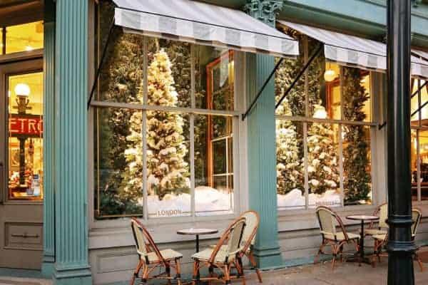 The elegant christmas windows at savannah's paris market shop with bistro tables outside.
