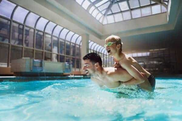 A dad and son splash in the glass atrium and pool at the fairmont olympic seattle.