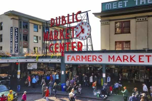 The clock, neon sign and busy stalls of pike place public market in downtown seattle.