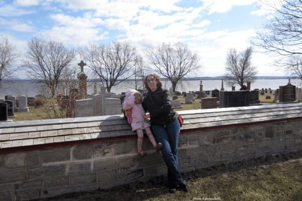 Mother and child in front of a scenic graveyard on ile d'orleans