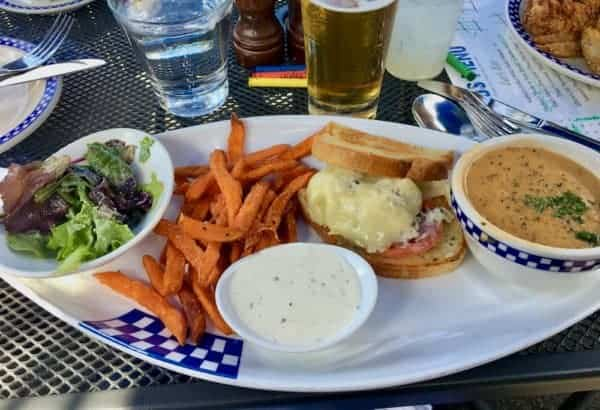 A crab sandwich with sweet potato fries, a green salad and bowl of chowder at duke's seafood.