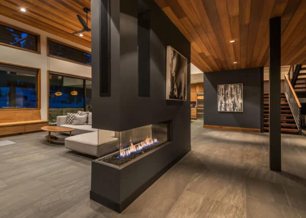 modern living space featuring an elegant two-sided plaster fireplace as half wall room divider