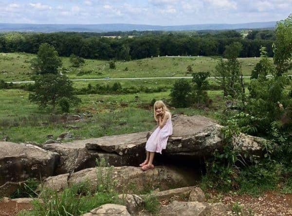 A child sits on a rock at little roundtop, bored.