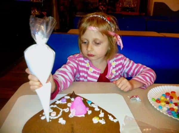 A girl decorates a giant heart cookie at gingerbread university in riverhead.