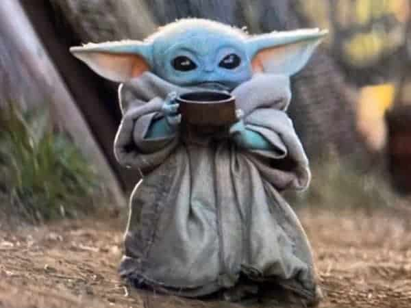 Baby Yoda holding a cup of soup