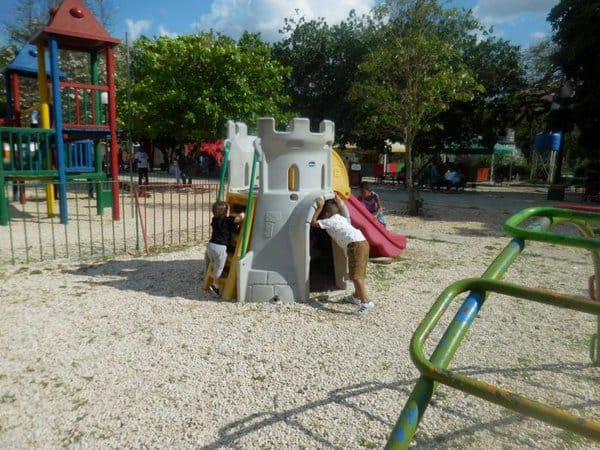A toddler takes a playground break from sightseeing in havana