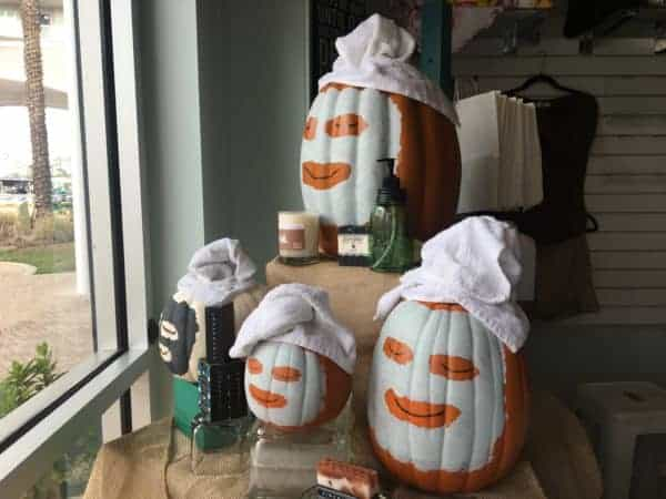 Pumpkins in facial masks decorate high cottons windows in fall.
