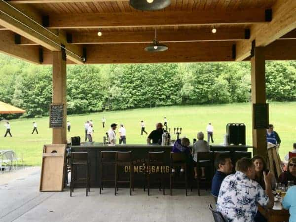 The outside bar and field behind Ommegang Brewery and tap house, a basebal game is happening.