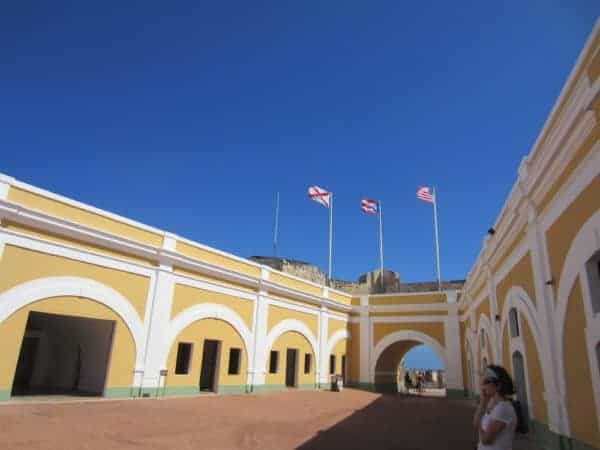 The colonial courtyard at the entrance to Puerto Rico's El Morro fort has yellow plaster walls and both the Puerto Rican and American flags flying.