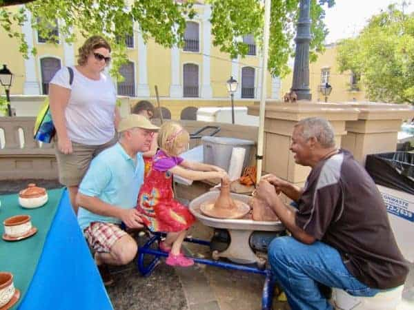 A young girl spins clay on a pottery wheel at a street stall in San Juan, Puerto Rico while the owner and passersby watch.