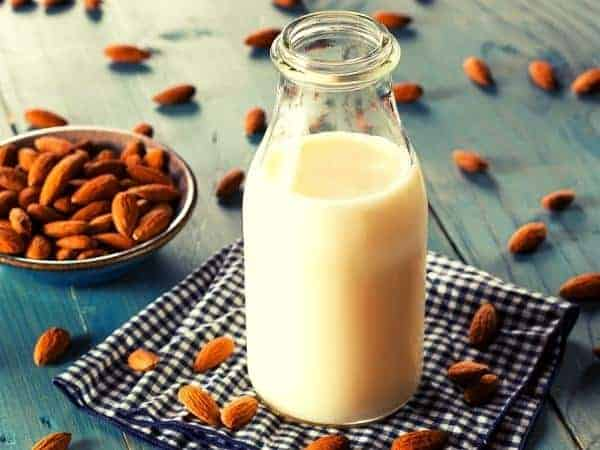 almond milk in a bottle on a blue cloth