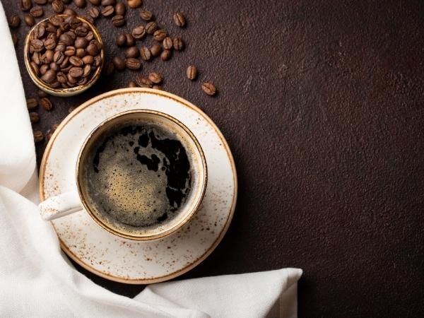 black coffee in a cup with coffee beans on the table