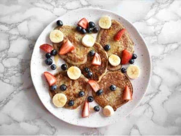 banana pancakes on a white plate with marble background topped with blueberries, strawberries and sliced banana