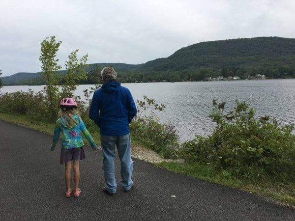 A dad and daughter pausing along a rail trail to admire the berkshire mountains and a lake