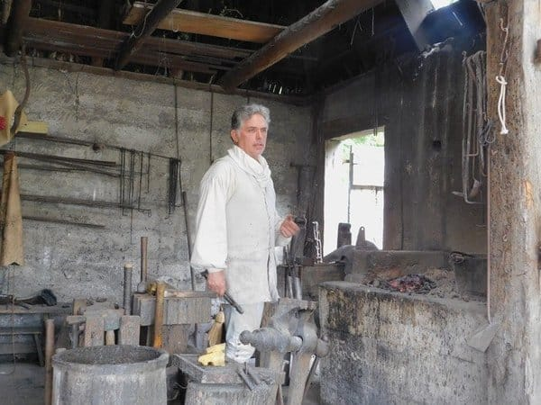 A volunteer does a blacksmithing demonstration in the colonial quarter