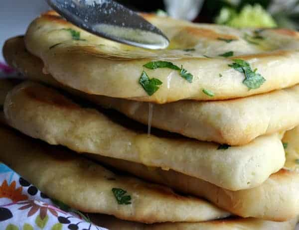 A stack of fresh garlic naan with parsley