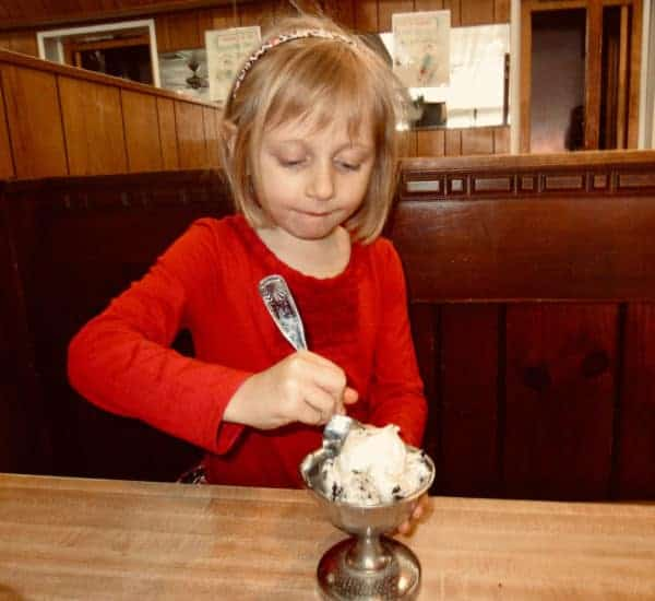 A girl eats housemade chocolate chip ice cream at sip 'n' soda in southampton, long island.