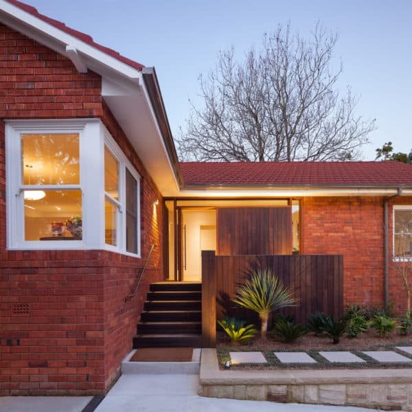 red brick house and red brick gable roof mixes color, wood, and metal elements for a timeless yet modern look